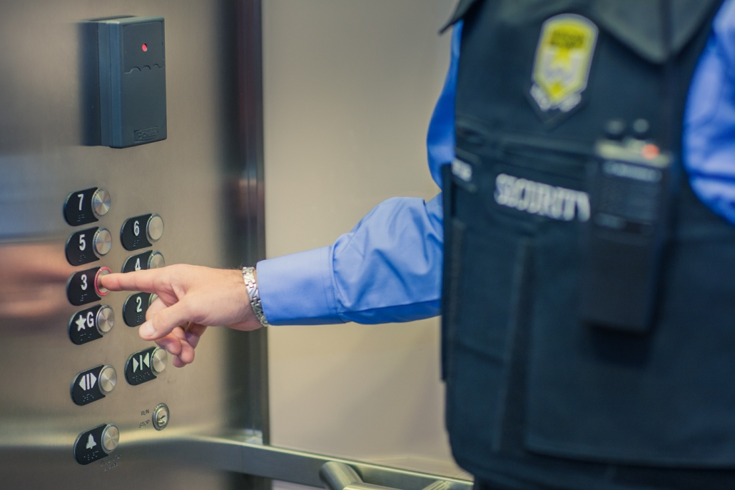 Wincon security guard pressing buttons in Toronto elevator