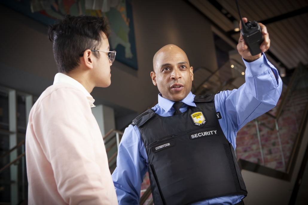 Retail or condo security guard helping customer with directions
