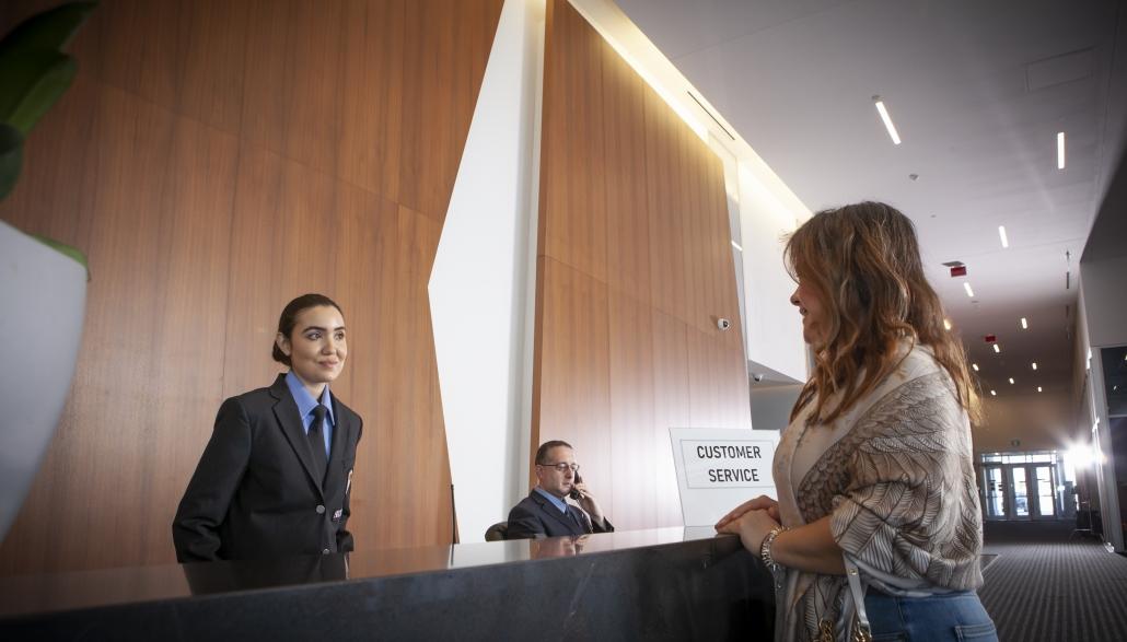 Condo concierge greeting tenant at front desk
